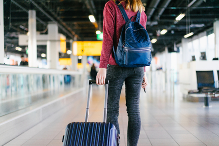 Cropped photo of female passenger with bag and backpack walking through the international airport terminal looking for her gate. Blurred background. View from the back.