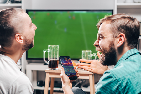 Photo for Two male buddies watching live football game broadcast on tv and celebrating money win after making bets online at bookmakers website. - Royalty Free Image