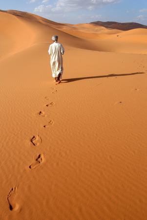 Lonely Berber man going ahead through the Sahara Desert in Morocco