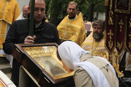 PRAGUE, CZECH REPUBLIC - MAY 28, 2012: Orthodox believer kisses the miracle-working icon of the Virgin Mary in front of the Dormition Church at the Olsany Cemetery in Prague, Czech Republic.