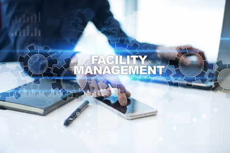 Businessman is working in office, pressing button on virtual screen and selecting facility management.