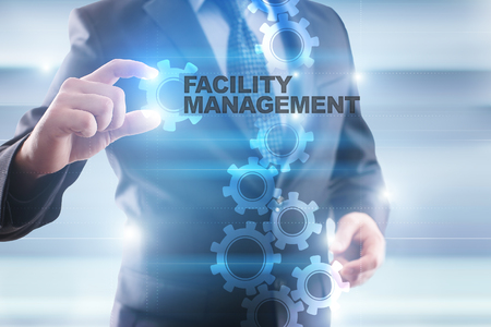 Businessman selecting facility management on virtual screen.
