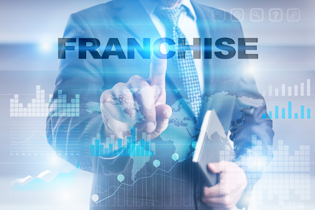 Businessman pressing button on touch screen interface and selecting franchise.