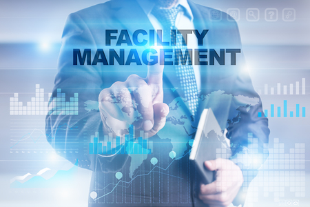 Businessman pressing button on touch screen interface and selecting facility management.