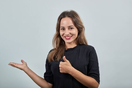 Foto de Cute young brunette woman in black t-shirt, blue jeans with belt on gray background, happy smiling girl gives a thumbs up and points the direction with hand - Imagen libre de derechos