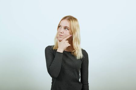 Photo for Young Blonde Woman In Black Sweater On White Background, Dreamy Girl Touches Her Chin And Thinks. The Concept Of Smart People, Intellectuals, Elite Of Society - Royalty Free Image