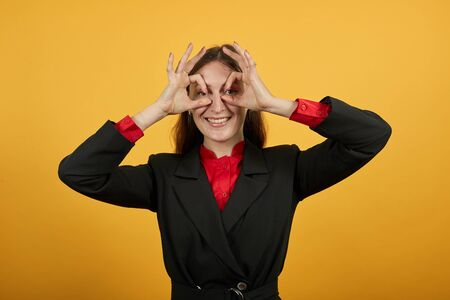 Young Attractive Brunette Woman In Black Stylish Suit, Red Shirt On Yellow Background, Funny Girl Holds Fingers Near Her Eyes, Imitates Glasses. The Concept Of People Who Fool Around Is Happy