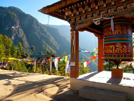 View of the Taktshang monastery in Paro (Bhutan) with prayer flags and a prayer wheel in the front