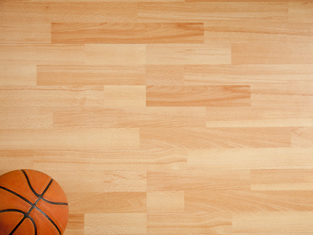 An official orange ball on a hardwood basketball courtの写真素材