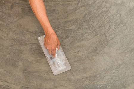 Photo pour Close up of hand using steel trowel to finish wet concrete floor of polished concrete surface - image libre de droit