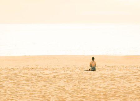 Foto de Woman traveler doing sit on tropical beach in vacation, Sunset. - Imagen libre de derechos
