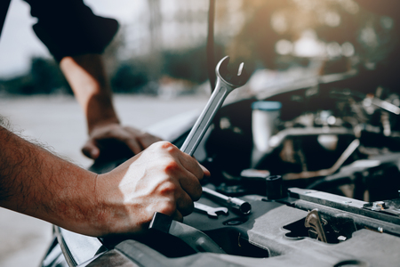 Photo for Car mechanic is holding a wrench ready to check the engine and maintenance. - Royalty Free Image