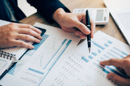 Foto de The accounting staff of the company are jointly analyzing the graph of the expenses on the desk in the office. - Imagen libre de derechos