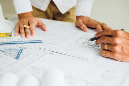 Photo for Two partnership architects or engineering working with blueprints and discussing project together at the meeting in the office. - Royalty Free Image