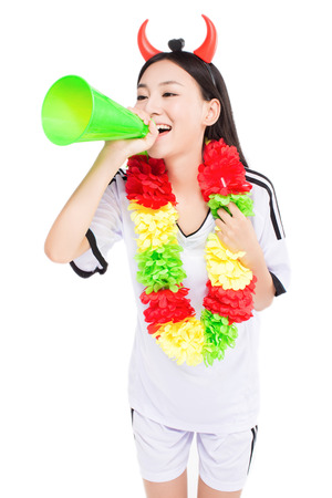 uniformed cheerleader a pose with a megaphone isolated on white.