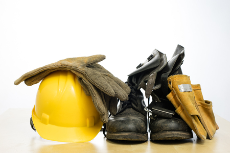 Protective helmet and work boots on a wooden table. Safety and health protection accessories for construction workers. White isolated background.