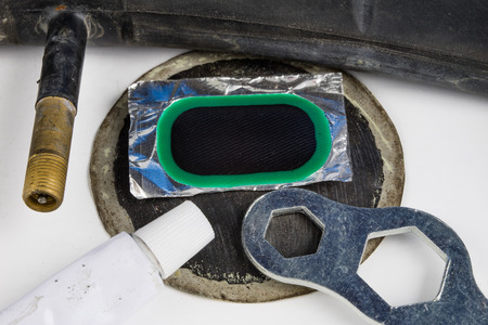 Bicycle tube, glue and patches in the workshop. Repairing a damaged wheel in a bike. Light background.
