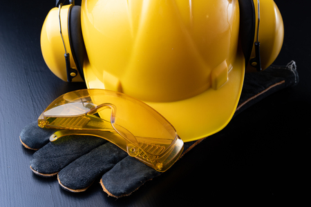 Photo pour Helmet and accessories for construction workers. Accessories needed for work on the construction site. Dark background. - image libre de droit