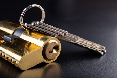 Photo for A new door lock on a dark background. A patent and keys to secure the front door. A black background. - Royalty Free Image