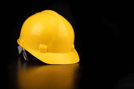 Photo pour Yellow helmet on a dark workbench. Protection accessories for construction workers. Dark background. - image libre de droit