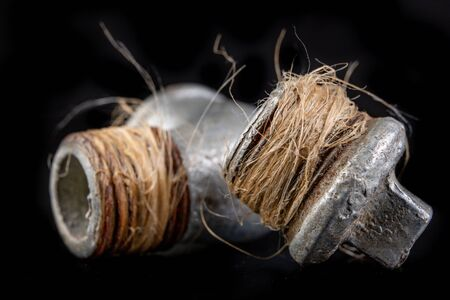 Oakum wrapped in a steel tube. Hydraulic accessories used for minor repairs. Dark background.