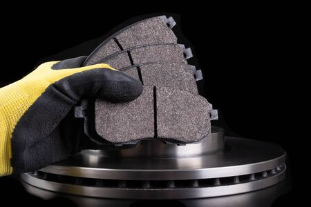 Photo pour Brake pad for a passenger car in the hand of a mechanic. New spare parts for car repairs. Dark background. - image libre de droit