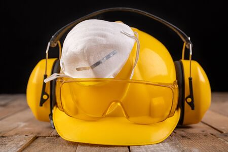 Photo pour Workwear and protective mask on a wooden table. Protective accessories for the production worker. Dark background. - image libre de droit