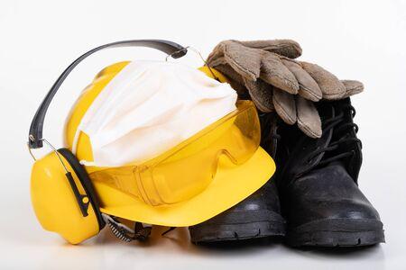 Photo pour Protective helmet, boots, gloves and flu mask. Building accessories during the plague. Light background. - image libre de droit