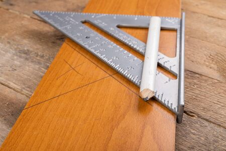 Photo pour Drawing a line in a carpentry shop using an angle bar. Small carpentry work in the workshop. Light background. - image libre de droit