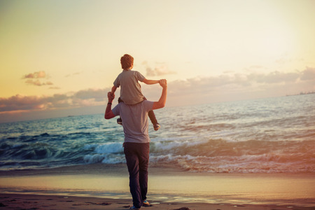 Foto de Happy father and son having quality family time on the beach on sunset on summer holidays. Lifestyle, vacation, happiness, joy concept - Imagen libre de derechos
