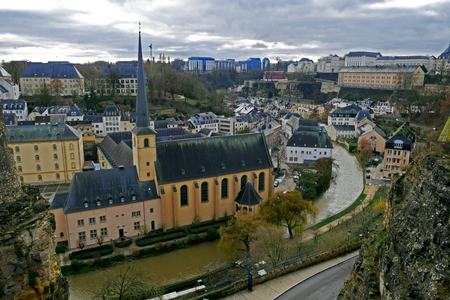Luxembourg City view from Le Chemin de la Corniche or Balcony of Europe. Alzette river, church of St Jean du Grund and Abbey of Neumunster