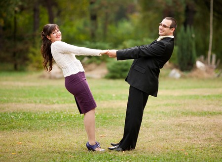 Happy young couple dancing outdoor in a park