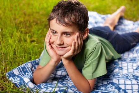 Closeup portrait of a happy boy smiling, lying on a blanket outdoor in the grass