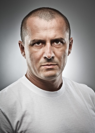 Fine art portrait of a menacing man, studio close up