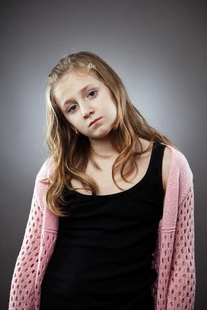 Sad girl studio closeup portrait on gray background