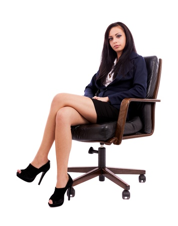 Full length portrait of a beautiful hispanic businesswoman sitting on an armchair isolated on white background