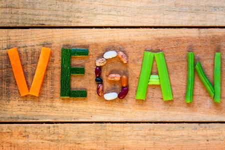 Photo pour vegan word with wood background - food - image libre de droit