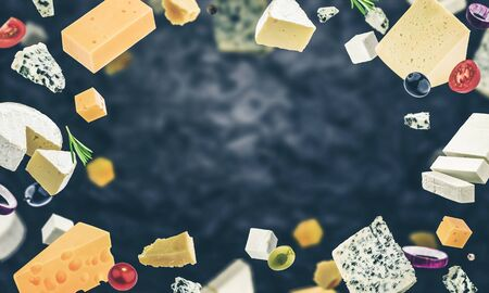 Cheese frame with space for text, isolated on black background with copy space, different types of cheese flying with herbs and spices, photo filtered in vintage style
