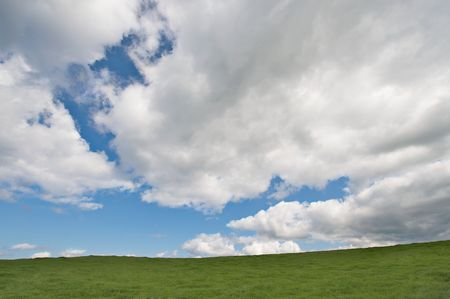 Green field and the blue sky with clouds