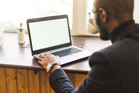 Foto de Young handsome dark-skinned businessman in a cafe working behind a laptop with a cup of tea. - Imagen libre de derechos
