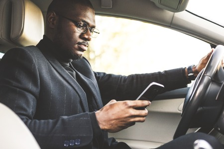 Photo for A businessman driving a expensive car holds a mobile phone in his hand. Hasty life. - Royalty Free Image