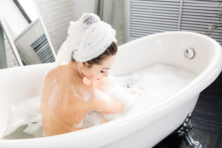 Photo pour A young attractive girl relaxes in the bathroom and rests against the backdrop of a beautiful light interior. Spa treatments for beauty and health with skin care - image libre de droit