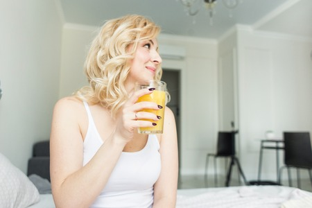 Photo pour Attractive blonde woman sits on the edge of the bed at home and holds a stocker with orange juice in her hand. Morning mood and vigor - image libre de droit