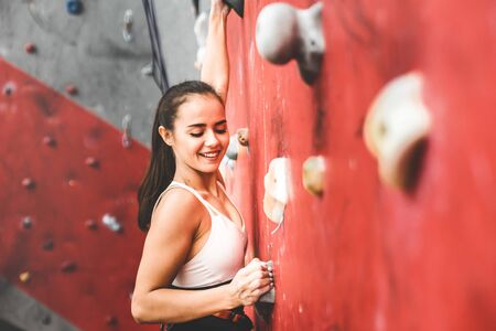 Photo pour Sportswoman climber moving up on steep rock, climbing on artificial wall indoors. Extreme sports and bouldering concept - image libre de droit
