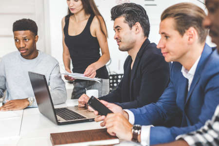 Photo for A team of young office workers, businessmen with laptop working at the table, communicating together in an office. Corporate businessteam and manager in a meeting. coworking. - Royalty Free Image