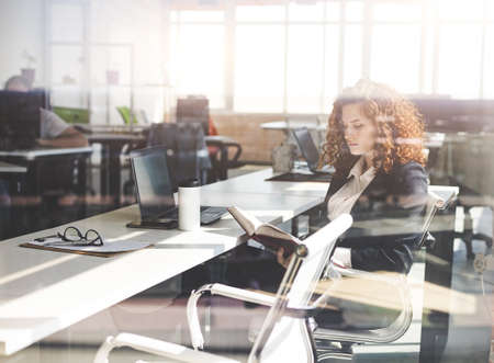 Photo pour Portrait of a beautiful young business woman with red curly hair working productively in the office. Successful career and staff of a large company - image libre de droit