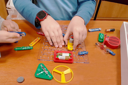 Photo for Children play an electro-mechanical constructor. Edukatsiya growing generation. Electrical circuits. Multi-colored toys for training and development of boys and girls. Physics for beginners. - Royalty Free Image
