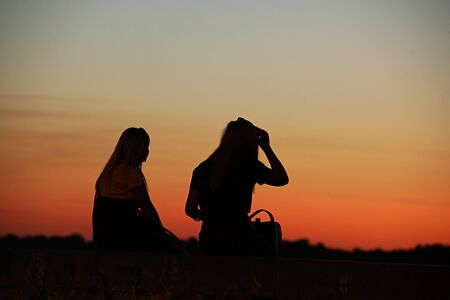 Photo pour The dark power of two girls against the backdrop of a crimson sunset. A play of colors and darkness. Photographing in the dark with low light. Girlfriends romantically relax in the evening. - image libre de droit