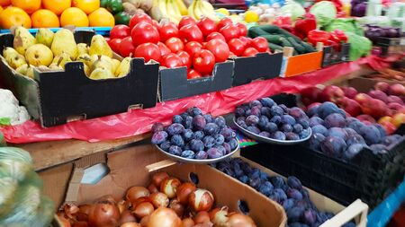 Photo for A variety of vegetables and fruits lying on a market counter for sale by a customer. Trade in agricultural products. Nitrates and pesticides. Genetically modified food. Farm fruits. Fiber and vitamins. - Royalty Free Image