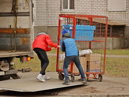 Foto de Two workers are loading a trolley with a cage for transporting goods onto the lift of a truck for transportation. Automation of manual work of loaders. Elevator platform on the rear side of the road trailer body. Raise up. - Imagen libre de derechos